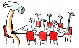 Salle de réunion, à la présidence, un marteau, les autres convives sont des clous. Mushroom, cabinet de recrutement, chasseurs de têtes